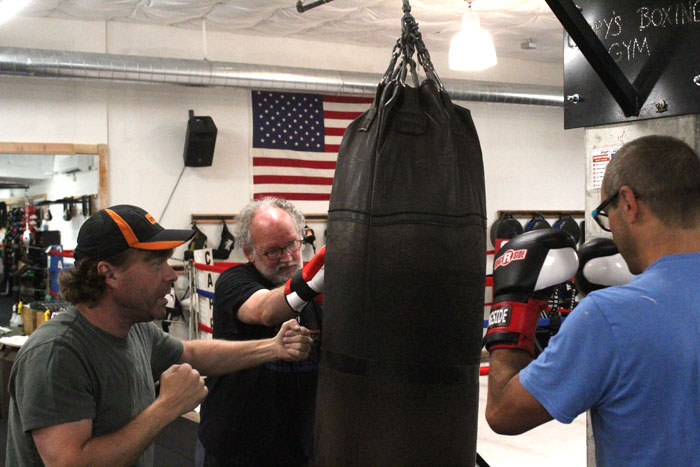 Longtime Cappy's coach Mike Priebe instructs two boxing students on Tuesday, July 17.