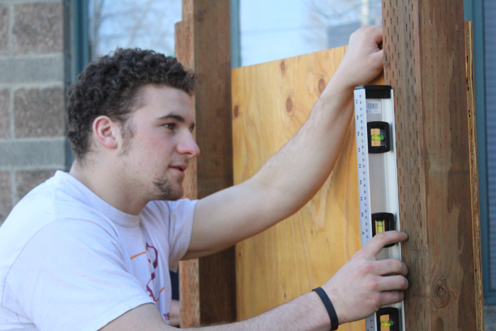 Photos by Brandon Macz: O'Dea High School senior Miles Krauter gets his bulletin board level during its installation outside the Bailey-Boushay House on Friday, March 16.